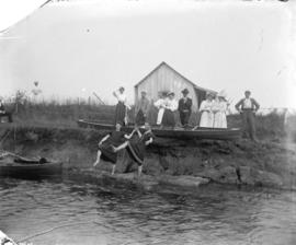[Men and women assembled near shore at Linn's cottage]