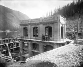 [Four men standing outside partially constructed gate house for Buntzen Lake Power Plant number two]