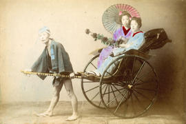 [Studio portrait of man pulling a rickshaw carrying two young women in traditional Japanese dress]
