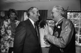 Unidentified man and Norman Young (right) talking indoors at Centennial birthday party