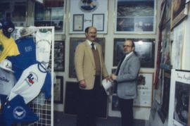 Mike Harcourt and unidentified man in front of gift display