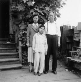 Gum May Yee, Guy Yee, and Foon Wong at the entrance to a house