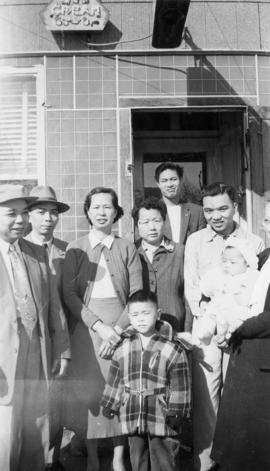 Vernon and Paul Yee with a group of Chinese people in front of Gordon Yee's café in Naicam, ...
