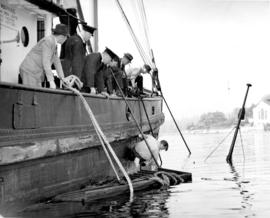 "[Men attempting to salvage the tugboat ""Ella McKenzie""]"