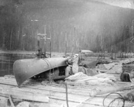 [A man resting on a dock at a logging camp]