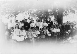 [Group of men, women, and children at a picnic table under a tree]