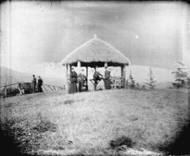 [Men and women around gazebo with thatched roof at Prospect Point]
