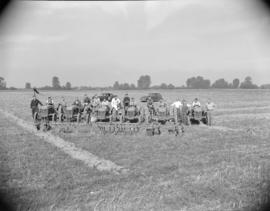 [Men on tractors lined up in a field]