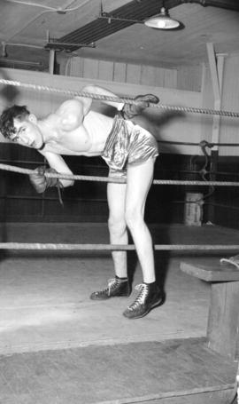 [Portrait of Jimmy Crook, boxer, climbing through ropes into the ring]