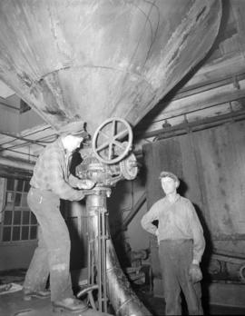 [Two men operating a machine at] Pacific Mills