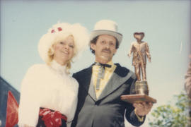 Unidentified woman and man wearing historical costumes holding statue