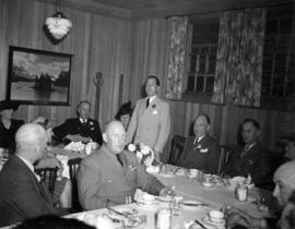 Dignitary speaking at V.E.A. luncheon as J. Dunsmuir, J.W. Cornett, and other guests listen