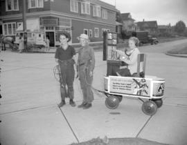 [Boys pulling a wagon in which a girl sits playing as a telephone operator as part of an advertis...