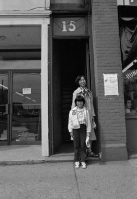 Woman and child at entrance to 15 East Pender Street