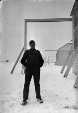 James Crookall outside hangar [in] snow [at Camp] Everman