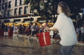 """Giant Fire Drill"" participant running with bucket of water"