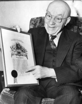 [Dr. Frank Gorlick holding his Vancouver Daily Province Pioneer's Certificate]