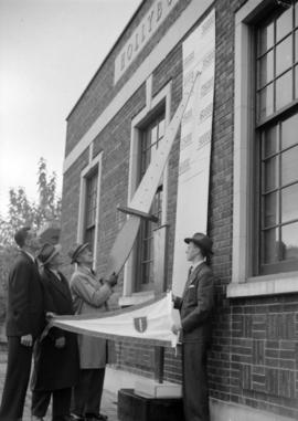 [Men setting up a fundraising promotion display on the side of a building]