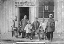 [Family in traditional clothing in front of Wah Chong Washing and Ironing]