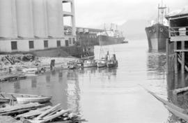 [Fishing boats and freighters docked at grain elevator]