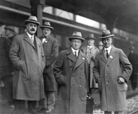 [Group portrait of Alderman E.W. Dean and Mayor L.D. Taylor greeting visitor at train station]