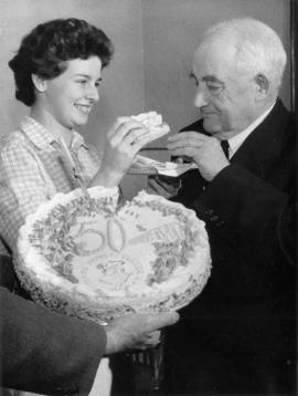 [Woman feeding] Major J.S. Matthews Golden Jubilee bank account cake 1909-1959