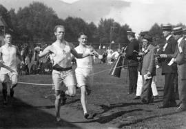 [Three men crossing the finish line after a race]