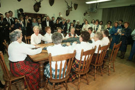 Group of women wearing kilts seated at table singing and holding a piece of Centennial tartan fabric