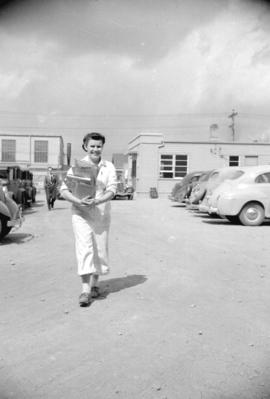 [Woman carrying papers through the parking lot of the Boeing plant on Sea Island]