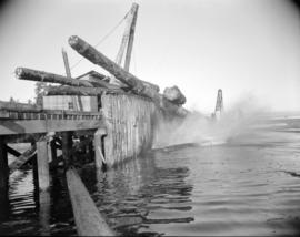 [Logs falling off a wharf into the water at H.R. MacMillan Co.]