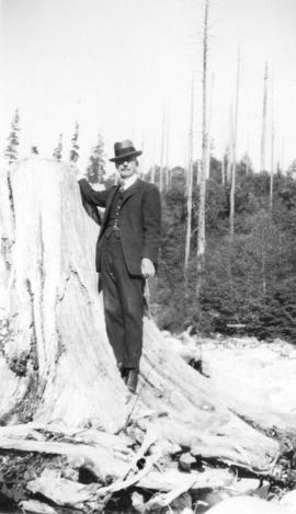 [L.D. Taylor standing next to large tree stump]