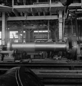 [View of Vancouver Engineering Works showing worker manufacturing a large pipe]