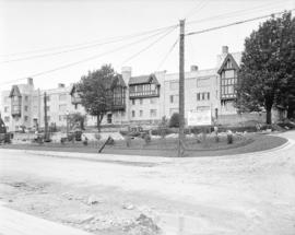 [Men landscaping grounds and Tudor Manor apartments on Pacific Street]