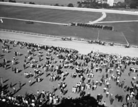 Crowd watching a horse race at P.N.E. racetrack