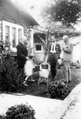 [George J. Fowler, Mary Louise, Ted and L.D. Taylor outside in yard]