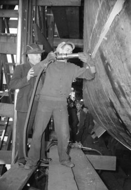 [Man with rivet gun at work on boat in Burrard Drydocks]