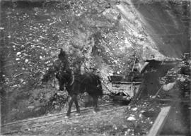 [Horse dragging cart out of partially excavated tunnel for Buntzen Lake Power Plant number one]