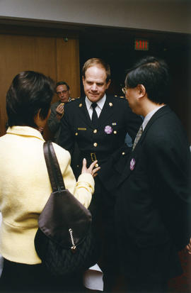 [Wendy Au] talking with two unidentified men at International Day to End Discrimination reception