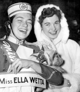 "[Two young women holding ""Ella Wetta"" a Grey Cup mascot from Regina]"