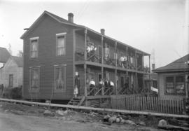 [Men, women, and children assembled on upper and lower porches of house at 1906 Grant Street]
