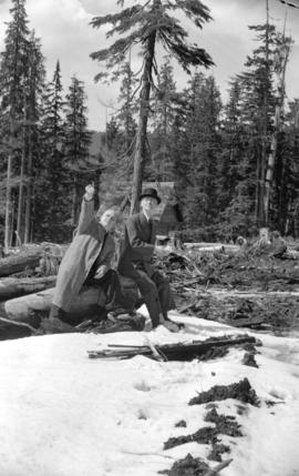 [Premier John Hart and a man sitting in a cleared area near the cabin on Hollyburn mountain]