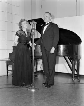[Man and woman standing by a piano at a CJOR microphone]