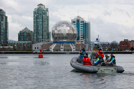 Torchbearer 292 Andrew McLean carries the flame on a RHIB past Science World in Vancouver, BC