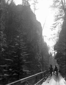 [Men standing on flume in Capilano Canyon]