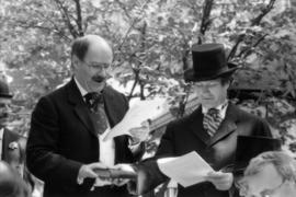Mike Harcourt and unidentified man reading from script