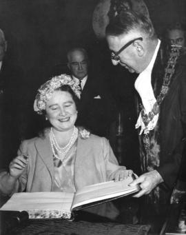[Her Majesty Queen Elizabeth the Queen Mother signs the guest book in the Mayor's office]