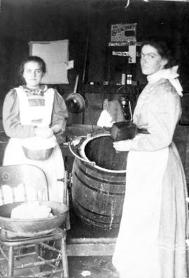 [Two women in a kitchen, churning butter]