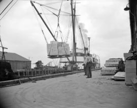 [Boxes of food being loaded onto a cargo boat at the Evans, Coleman and Evans, Ltd. pier]