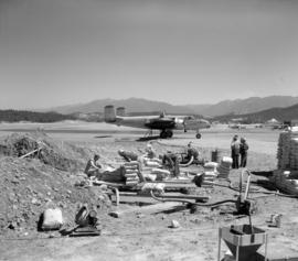 [Crew loading water mixed with fire control chemicals from large pits into a water bomber at the ...