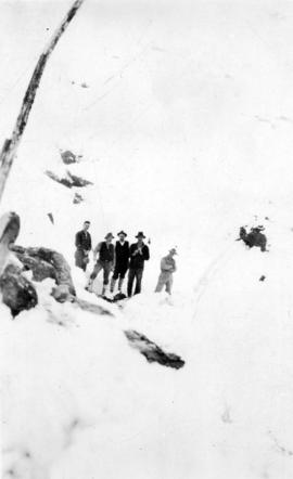 [Group photograph of men standing on mountain in snow]